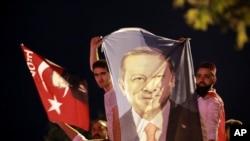 មនុស្សម្នាកាន់បដាដែលមានរូបរបស់លោកប្រធានាធិបតីតួកគី Recep Tayyip Erdogan សាទរនៅខាងក្រៅគណបក្សយុត្តិធម៌ និងអភិវឌ្ឍន៍ នៅក្នុងក្រុងអ៊ីស្តង់ប៊ុល កាលពីថ្ងៃទី២៤ ខែមិថុនា ឆ្នាំ២០១៨។