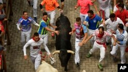 Revelers run with a Puerto de San Lorenzo fighting bull during the third running of the bulls at the San Fermin Festival, in Pamplona, Spain, July 9, 2017. Revelers from around the world flock to Pamplona every year to take part in the eight days of the running of the bulls.