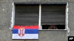 Čovek na prozoru stana tokom trajanja 60 sati dugog policijskog časa u Beogradu, 10 aprila 2020. (AP Photo/Darko Vojinović)