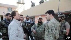 El jefe de la policía de Kunduz, Mohammad Qasim Jangalbagh, izquierda, conversa con fuerzas especiales de Afganistán y Estados Unidos.