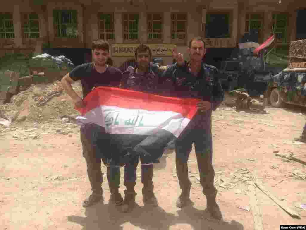 سربازان عراقی با پرچم عراق در جادۀ در شهر موصل که تا چند روز پیش زیر تسلط داعش بود