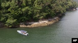 """A boat belonging to Animal Heart Protectors is anchored off Furtada Island, popularly known as """"Island of the Cats,"""" where they deliver food and water to the cats in Mangaratiba, Brazil, Tuesday, Oct. 13, 2020. (AP Photo/Mario Lobao)"""