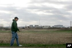 FILE - A man walks past a Marquis Energy LLC ethanol plant near Hennepin, Ill., April 4, 2007.