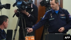 A Russian military official points to the flight recorder from the Russian Sukhoi Su-24 bomber that was shot down by a Turkish jet on Nov. 24, during a briefing on decoding the black boxes, Moscow, Dec. 18, 2015.
