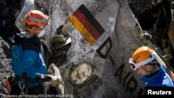 French gendarmes work near debris from the Germanwings crash, near Seyne-les-Alpes, in this photo released by the French Interior Ministry April 1, 2015. A German flag is on the wreckage.