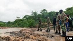 On voit des soldats inspecter les dégâts sur une route lors d'opérations de recherche et de sauvetage à la suite d'inondations dévastatrices et de glissements de terrain provoqués lorsque le cyclone Idai a frappé le Zimbabwe à Chimanimani, dans la provinc