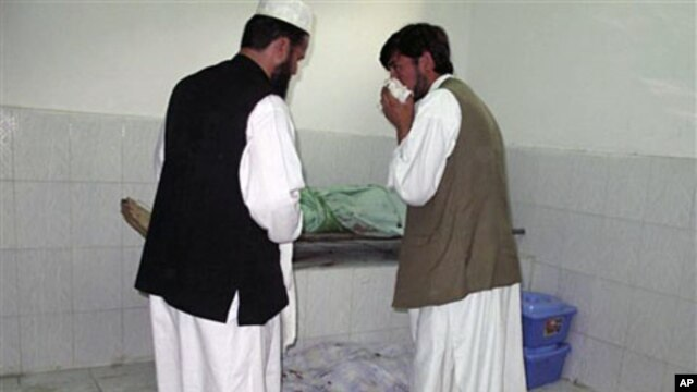 Afghans stand by bodies of people killed in a bombing in a mosque in Taloqan, north of Kabul Afghanistan, 08 Oct 2010