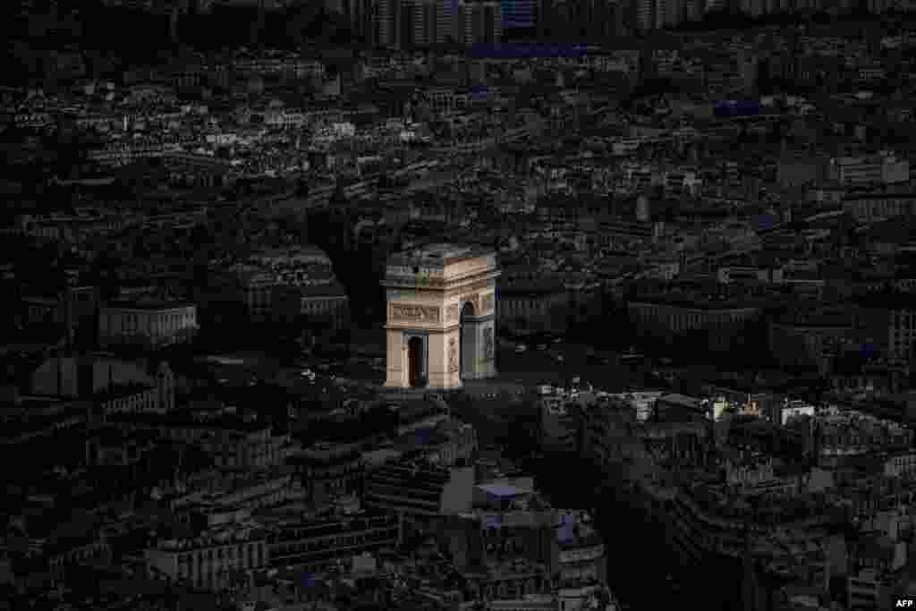 A ray of light shines on the Arc de Triomphe in Paris, France.