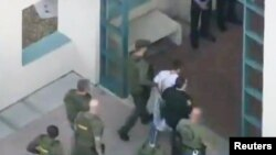 Police escort a suspect into the Broward Jail after checking him at the hospital following a shooting incident at Marjory Stoneman Douglas High School in Parkland, Florida, Feb. 14, 2018 in a still image taken from a video.