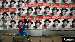 A schoolgirl walks past campaign posters in support of Nigeria's President Goodluck Jonathan along a road in Ikoyi district in Lagos, Feb. 13, 2015.