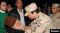 압델 파타 엘 시시 이집트 국방장관이 지난 26일 수도 카이로에서 최근 피살된 군인들의 장례식에 참석해, 유가족을 위로하고 있다.