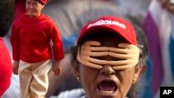 Una mujer simpatizante del presidente Nicolás Maduro, usa un juego de manos sobre su cara y un muñeco de Hugo Chávez durante un evento de campaña.