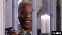 Cố Tổng thống Nam Phi Mandela cầm cây nến biểu tượng thiên niên kỷ, đứng sau song sắt nhà tù ở Robben Island, nơi ông bị giam giữ. (Ảnh tư liệu, 31/121999).