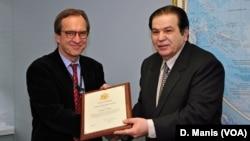 O Ντέιβιντ Ένσορ βραβεύει τον Γ. Μπίστη για το έργο του.