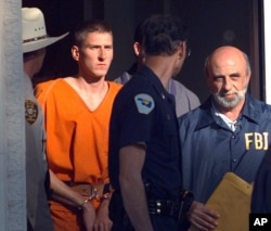 FILE - In this April 21, 1995 file photo, Timothy McVeigh is led out of the Noble County Courthouse by state and federal law enforcement officials in Perry, Oklahoma, after being identified as a suspect in the bombing of the Oklahoma City Federal building. McVeigh was eventually convicted of the bombing and executed.