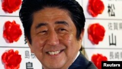 Thủ tướng Nhật Bản Shinzo Abe mĩm cười khi ông cài bông hồng nhỏ bằng ruy băng lên bảng tên của một ứng cử viên được dự kiến đắc cử, 21/7/13
