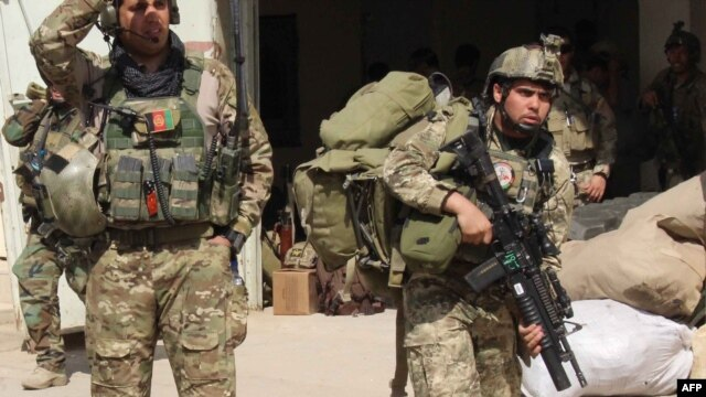 FILE - Afghan special forces arrive at the airport as they launch a counteroffensive to retake the city from Taliban insurgents, in Kunduz, Sept. 29, 2015.