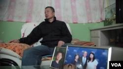 中國著名維權律師高智晟2015年在陝西的窯洞住宅里聽記者講話,旁邊是他兒子的照片和女兒與美國前總統布殊的合影