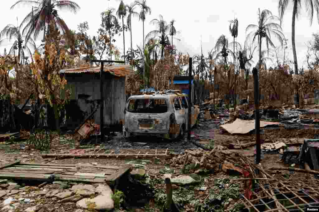 A car is seen near a house that was burnt down during the last several days of violence in Maungdaw, Myanmar.
