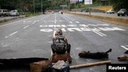 Un membre de l'opposition bloque la route à Caracas, Vénézuela, le 30 juillet 2017.