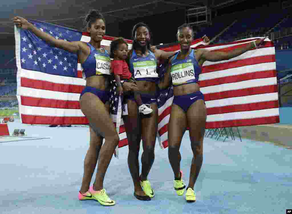 Gold medal winner Brianna Rollins, silver medal winner, Nia Ali, and bronze medal winner Kristi Castlin,all from the United States, celebrate with their country's flag.