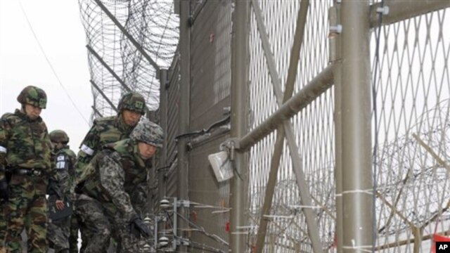 General Hwang Eui-don (R), Chief of the General Staff of South Korean Army, checks the fence of the Demilitarized Zone between the two Koreas as he patrols with Army soldiers in Paju, South Korea, 01 Dec 2010