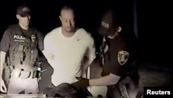 Tiger Woods is seen handcuffed and searched by police officers in this still image from police dashcam video in Jupiter, Florida, May 29, 2017.