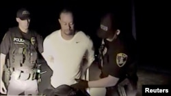 FILE - Tiger Woods is seen handcuffed and searched by police officers in this still image from police dashcam video in Jupiter, Florida, May 29, 2017.