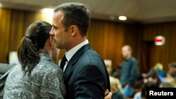 Oscar Pistorius habla con su hermana Aimee durante el quinto día del juicio por el asesinato de su novia.