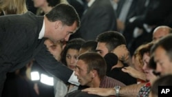 Spanish Prince Felipe, left consoles family members of the victims of the earthquake in Lorca, Spain, May 13, 2011
