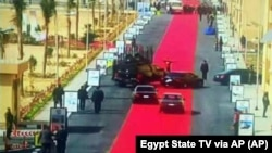 Egyptian President Abdel-Fattah el-Sisi's motorcade drives on a red carpet during a trip to open social housing projects in a suburb of Cairo, Egypt.