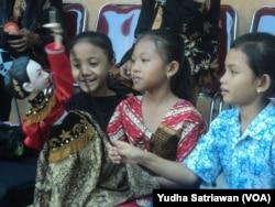 Tiga siswa SD sedang bermain menggunakan wayang golek di SD Negeri 26 Solo dalam kegiatan Wayang Masuk Sekolah, Rabu (18/7).