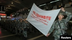Members of a medical aid team of People's Liberation Army (PLA) carry a flag during their departure ceremony at Beijing Capital International Airport, in Beijing as more than 200 soldiers from a military hospital departed for Africa to help fight Ebola, Nov. 14, 2014.