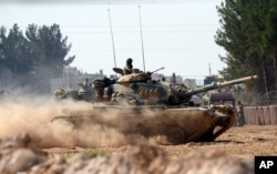 FILE - Turkish tanks head toward the Syrian border, in Karkamis, Turkey, Aug. 31, 2016.