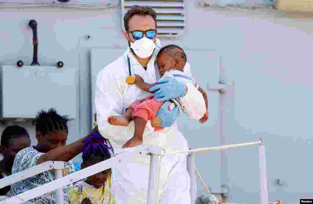 A doctor holds a baby as migrants disembark from Italian Navy ship Sirio in the Sicilian harbor of Augusta, Italy.