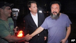 Activist artist Ai Weiwei (R) shakes hand with unidentified foreign journalists gathered outside his home in Beijing, June 22, 2011