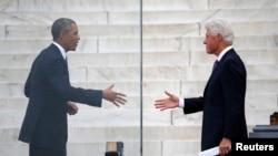 克林顿前总统在纪念华盛顿大游行50周年仪式中讲话后奥巴马总统上前和他握手。