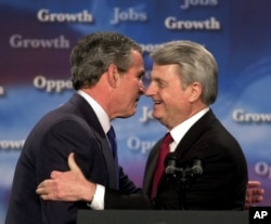 President George Bush, left, and U.S. Sen. Zell Miller, D-Ga., embrace as Bush is introduced at a program on Jobs and Economic Growth at Harrison High School in Kennesaw, Georgia, Feb. 20, 2003.