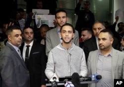 Ali Hassan, center, speaks at a news conference after his wife, Shaima Swileh, hidden, arrived at San Francisco International Airport in San Francisco, Dec. 19, 2018.