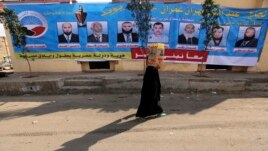 FILE - A woman walks past a campaign banner for the Nour party ahead of parliamentary elections, in Cairo,  November 27, 2011.