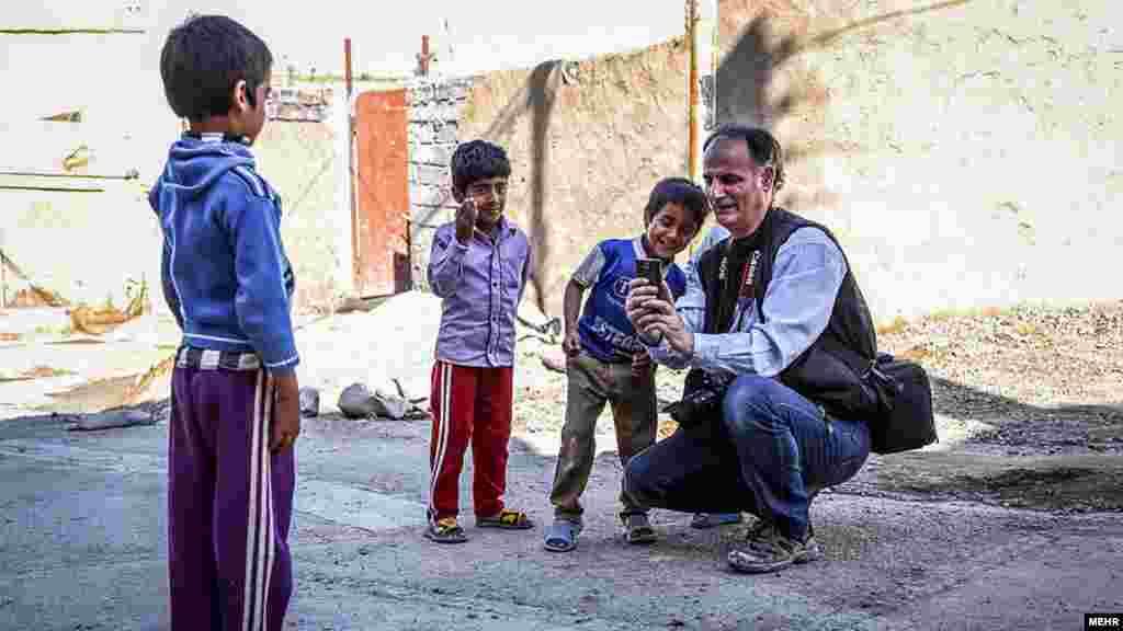 آقای عکاس، عکسی را که با گوشی اش گرفته، به کودکان نشان می دهد. در نوروز، تعدادی از عکاسان خبرگزاری مهر، با هدف انعکاس واقعیتهای منطقه محروم سیستان، به این استان سفر کردند. عکس: آرش شهرنورد، مهر