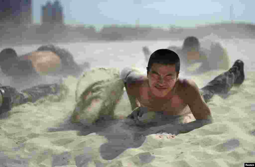 A paramilitary policeman crawls with his comrades in the sand during heat endurance training in Hefei, Anhui province, China. The temperature in Hefei reached 39 degrees Celsius (102.2 degrees Fahrenheit).