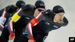 Denny Morrison, left, Jordan Belchos, center, Ted-Jan Blomen, right, of Canada, skate in the men's team pursuit competition at a World Cup speedskating event, Dec. 8, 2017, in Salt Lake City.