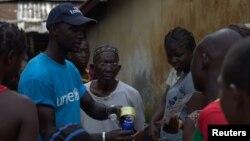 Seorang pekerja UNICEF (kiri) memberikan informasi mengenai Ebola terhadap masyarakat di Conakry, Guinea (foto: ilustrasi).