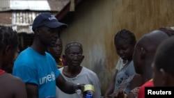 Một nhân viên của UNICEF chia sẻ thông tin với cư dân ở Conakry, Guinea về Ebola và những phương pháp tốt nhất để ngăn ngừa sự lan tràn của căn bệnh này.