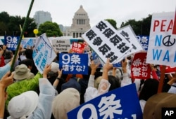 FILE - In this Aug. 30, 2015 file photo, protesters hold anti-war placards in front of the National Diet building during a rally in Tokyo. Japan holds an election on July 10, 2016, for the upper house of parliament that could affect the country's future.