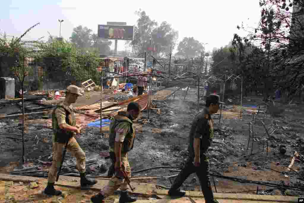 2013年8月15日,埃及军人走过开罗的穆尔西支持者最大营地被清场后的废墟