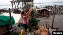 Nora Yara, a victim of super typhoon Haiyan, decorates a Christmas tree.