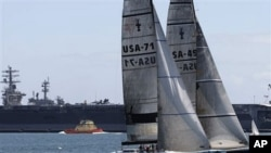 Two 12-meter America's Cup yachts sail past the USS Ronald Reagan in San Diego Harbor, 11 May 2010
