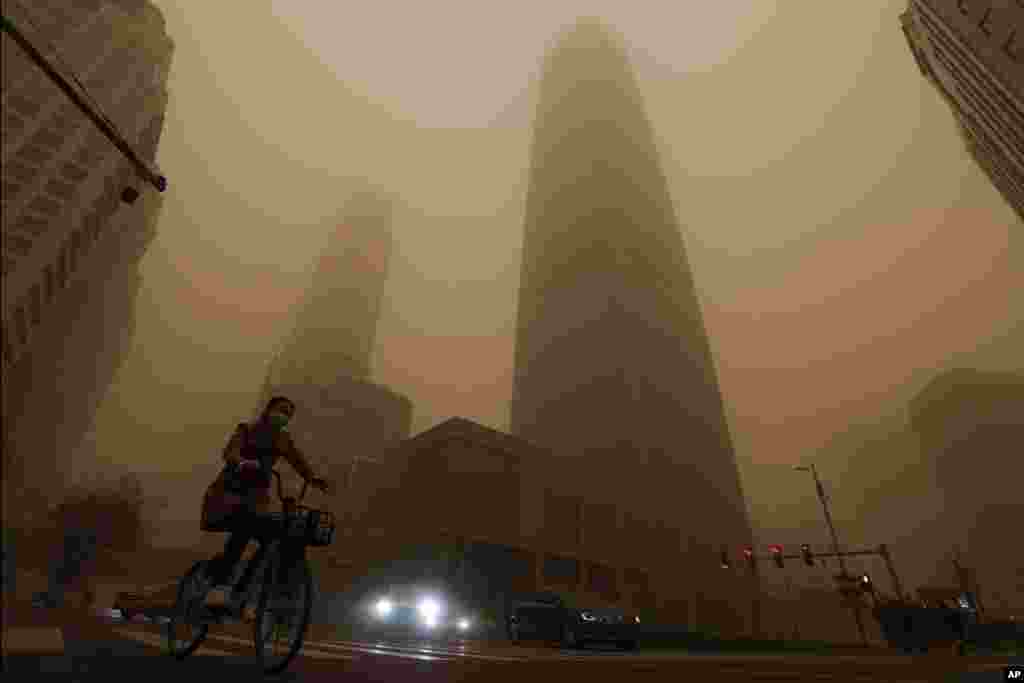 A cyclist and motorists move past office buildings amid a sandstorm during the morning rush hour in the central business district in Beijing, China.